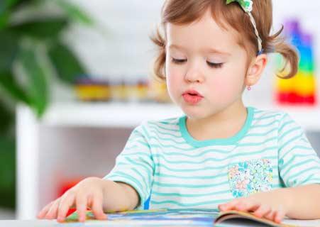 Çocuğuma İngilizce nasıl öğretebilirim konusu için kullanılan resimde, kitap okuyarak İngilizce öğrenmeye çalışan kız çocuğu görseli var.