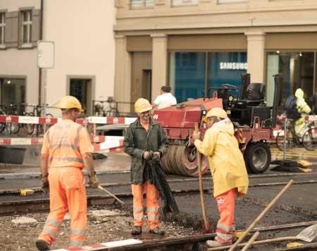 İş Güvenliği Uzmanı Nasıl Olunur sorusu için inşaat yerinde çalışan işçilere ait bir görsel. Şapka takmanın amacı işçilerin can güvenliğini sağlamak.