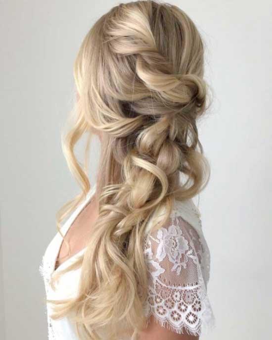 Uzun saç modelleri için kullanılan resimde, dalgalı ve dağınık örgülü uzun saça sahip çekici bir kadın var.