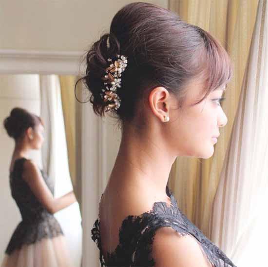 Gelin başı modelleri yazısı için kullanılan bu resimde, kaküllü ve topuz model kısa saça sahip gelinlik giymiş güzel bir kadın görseli var.