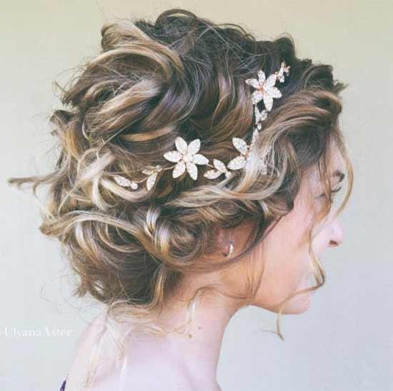 Gelin başı gelin saç modelleri yazısı için kullanılan bu resimde, çiçek taçlı, kısa ve kıvırcık saça sahip gelinlik giymiş güzel bir kadın görseli var.