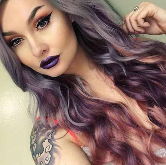 Ombre Saç Modelleri - Resimde mor ve pembe reng tonları uygulanarak ombre boyama tekniği ile boyalı uzun, dalgalı kadın saçı görseli var.