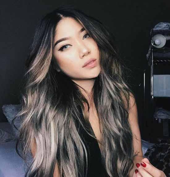 Ombre saç modelleri - Resimde, ombre boyama tekniği ile kül rengi ve kahverengi tonlarla boyalı, bir kadına ait uzun, dalgalı saç modeli var.