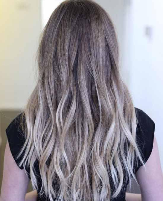 Ombre saç modelleri - Resimde, ombre boyama tekniği uygulanarak plaj sarısı renk tonlarıyla boyanmış, uzun, dalgalı kadın saçı görseli var.