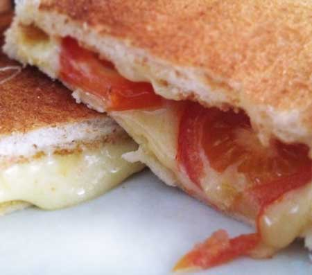 Tost yapımı için kullanılan resimde peynir, domates ve yarım ekmek ile hazırlanmış nefis tost görseli var.
