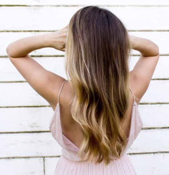 Ombre saç modelleri - Resimde kadına ait, ombre boyama tekniği ile koyu kahverengi ve sarı renk tonlarıyla boyalı, uzun ve dalgalı saç modeli var.