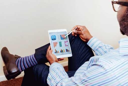 Dyned nedir konulu yzaı için kullanılan resimde, öğretmen, tablet üzerinden öğrencilerin İngilizce performansını değerlendiriyor.