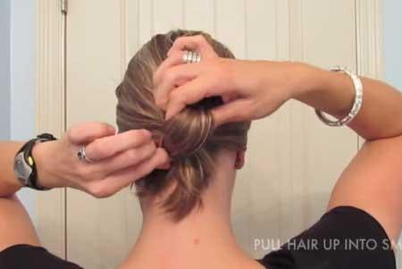 Topuz Saç Modelleri yazısı için kullanılan resimde, kadın saçını saç lastiğiyle topluyor. topluyor.