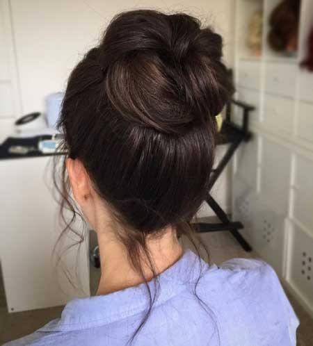 Dağınık Topuz Saç Modelleri yazısı için kullanılan resimde, tepeden topuz modele ve ince telli saçlara sahip güzel bir bayan görseli var.