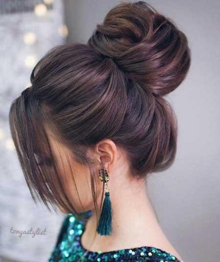 Dağınık topuz saç modelleri - Resimde, güzel bir kadının ince telli saçlarına tepeden dağınık topuz saç modeli uygulamış ve öndeki saça perçem verilmiş.