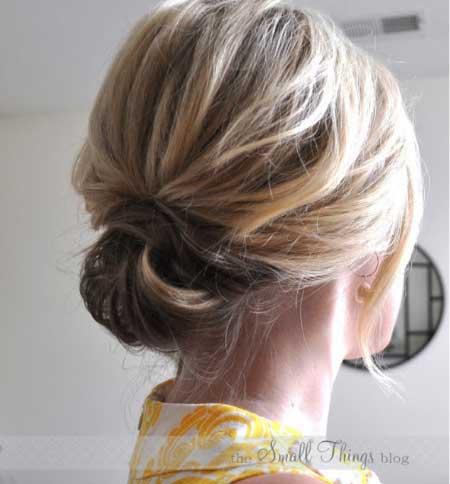 Dağınık Topuz Saç Modelleri yazısı için kullanılan bu görselde, dağınık topuz stili uygulanmış kısa saçlı bir bayan var.