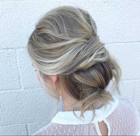 Dağınık Topuz Saç Modelleri - Resimde orta uzunlukta saçlarına dağınık topuz stili yapılmış kadın görseli var.