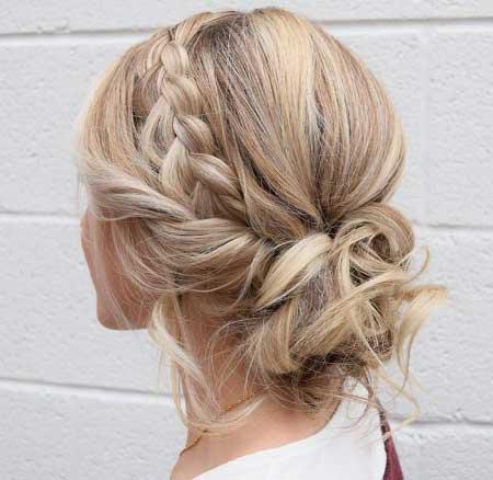 Dağınık Topuz Saç Modelleri yazısı için kullanılan resimde örgülü topuz saç stiline sahip çekici bir kadın var.
