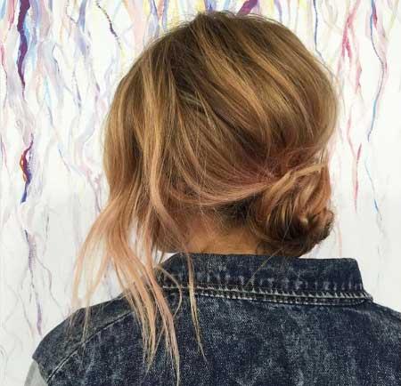 Dağınık Topuz Saç Modelleri - Resimde orta uzunlukta saça sahip kadına düşük topuz saç stili yapılmış.