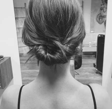 Dağınık Topuz Saç Modelleri yazısı için kullanılan resimde, orta uzunlukta saç sahip kadına topuz saç stili uygulanmış.