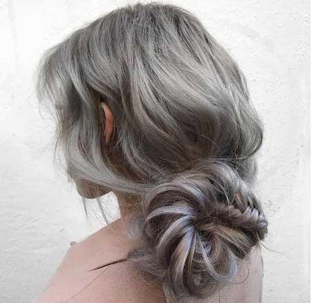 Dağınık topuz saç modelleri için kullanılan bu resimde, uzun, dalgalı ve dağınık topuz saça sahip çekici bir kadın görseli var.