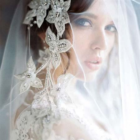 Düğün Saç Modelleri 2018 yazısı için öne çıkarılan bu resimde yüzünü beyaz tül ile örtmüş güzel ve çekici bir gelin var.