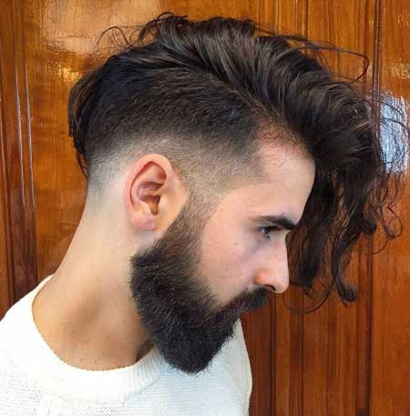Erkek Saç Modelleri 2019 yazısı için kullanılan resimde, kalp şeklinde yüze, kirli sakala, uzun, kaküllü saçlara sahip yakışıklı bir erkek var