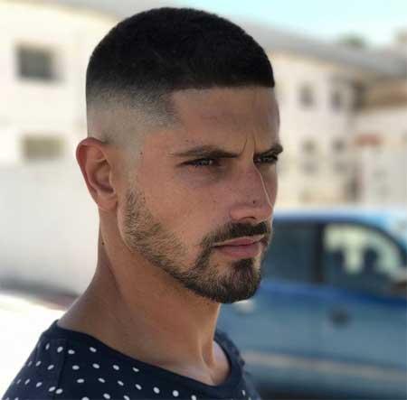 Erkek Saç Modelleri 2019 yazısı için kullanılan resimde, yanlar üstlere göre biraz daha kısa modern saç stiline sahip yakışıklı bir erkek var.