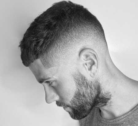 Erkek Saç Modelleri 2019 yazısı için kullanılan resimde, yanlar üstlere göre biraz daha kısa modern saç stiline sahip sakallı bir erkek var.