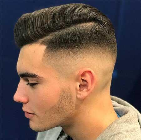 Erkek Saç Modelleri 2019 yazısı için kullanılan resimde, yanlar üstlere göre biraz daha kısa, yana ayrık saç stiline sahip genç bir erkek var.