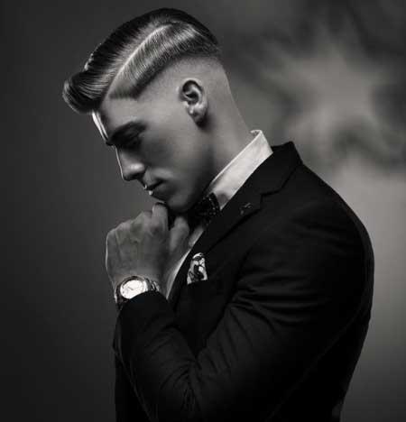 Erkek Saç Modelleri 2019 yazısı için kullanılan resimde, yanlar üstlere göre biraz daha kısa modern saç stiline sahip yan profil duran genç bir erkek var.