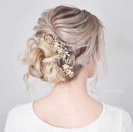 Düğün Saç Modelleri 2018 yazısı için kullanılan resimde, orta boy topuz saç stiline ve saçında çiçek taca sahip, gelinlik giymiş güzel bir gelin var.