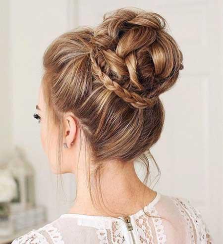 Düğün Saç Modelleri 2018 yazısı için kullanılan resimde, yeni, örgülü yüksek topuz saç stiline sahip, gelinlik giymiş güzel bir gelin var.
