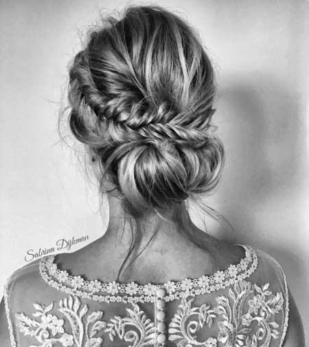 Düğün Saç Modelleri 2018 yazısı için kullanılan resimde, örgülü, modern ve yeni düşük topuz saç stiline sahip güzel bir gelin var.
