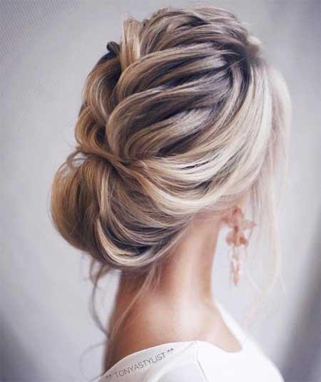Düğün Saç Modelleri 2018 yazısı için kullanılan resimde, yeni düşük topuz saç stiline ve parlak küpelere sahip, sade gelinlik giymiş güzel bir gelin var.