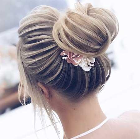 Düğün Saç Modelleri 2018 yazısı için kullanılan resimde, modern, yüksek topuz saç stiline ve çiçekli tokaya sahip gelinlik giymiş güzel bir gelin var.
