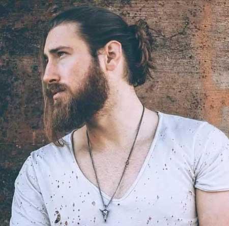 Erkek Saç Modelleri 2019 yazısı için kullanılan resimde, geriden topuzlu, önden kaküllü ve modern uzun saç stiline sahip, kirli sakallı bir erkek var.