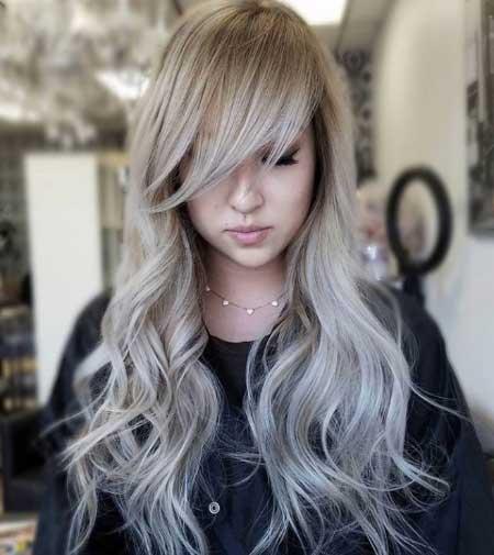 Uzun ince telli saçlar için saç kesim modelleri bayan - Resimde uzun, kahküllü, dalgalı ve hacimli ince telli saça sahip güzel bir kadın var.