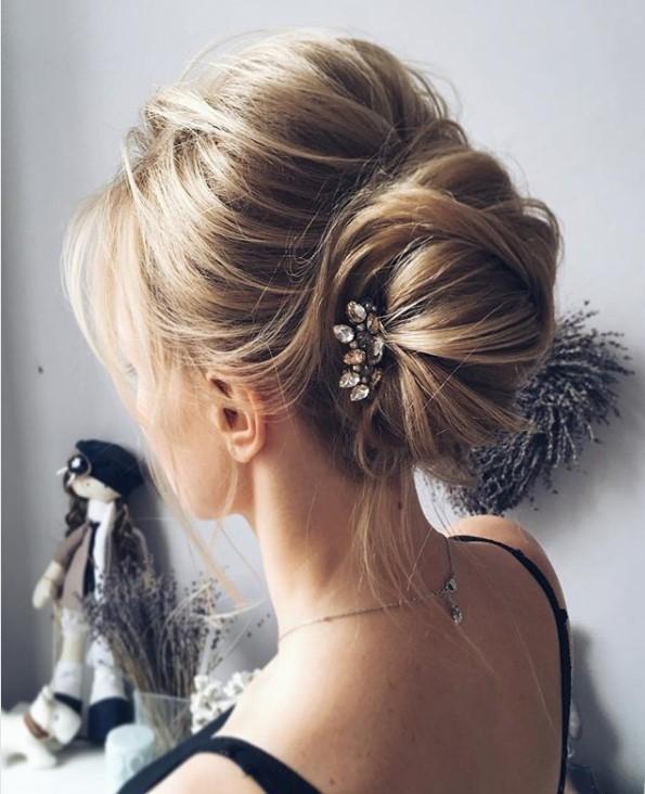 Uzun ince telli saçlar için saç kesim modelleri bayan - Resimde topuzlu, uzun ince telli saça sahip güzel bir kadın var.