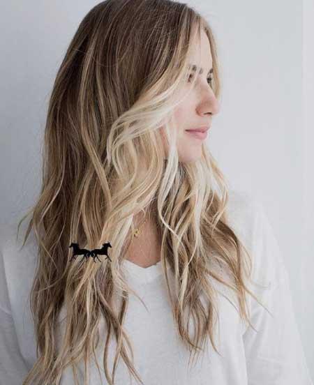 Uzun ince telli saçlar için saç kesim modelleri bayan - Resimde uzun, dalgalı ve hacimli ince telli saça sahip kumral bir kadın var.