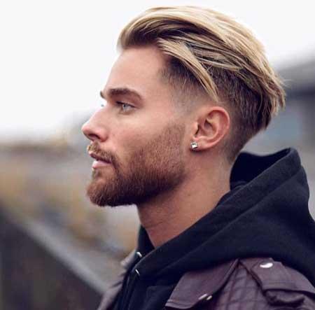 Erkek Saç Modelleri 2019 yazısı için kullanılan resimde, arkaya ve yanlara taranmış düz, uzun ve balyaj uygulanmış saç stiline sahip, kirli sakallı bir erkek var.